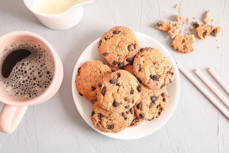 Platte mit geschmackvollen Schokoladensplitterplätzchen und -Tasse Kaffee auf grauem Hintergrund lizenzfreies stockbild
