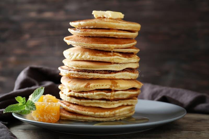 Platte mit geschmackvollen selbst gemachten Pfannkuchen und Honigkamm auf Tabelle lizenzfreie stockfotos