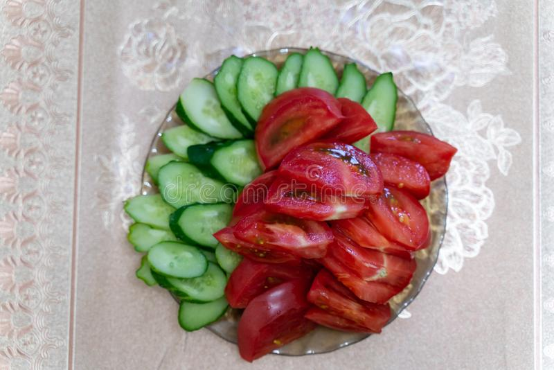 Platte mit geschnittenen Stücken frischen Tomaten und Gurken auf dem Tisch stockfotografie