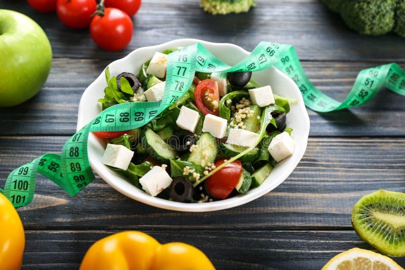 Platte mit gesundem frischem Salat und messendem Band auf Holztisch N?hren Sie Konzept stockfotos