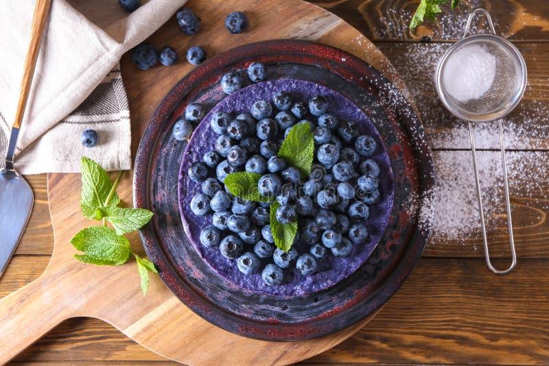 Platte mit köstlichem Blaubeerkäsekuchen auf Holztisch lizenzfreies stockbild