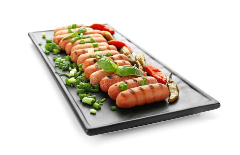 Platte mit köstlichen gegrillten Würsten, Paprikapfeffern und Kräutern auf weißem Hintergrund stockbild