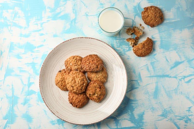 Platte mit köstlichen Hafermehlplätzchen und Glas Milch auf Farbhintergrund lizenzfreies stockfoto
