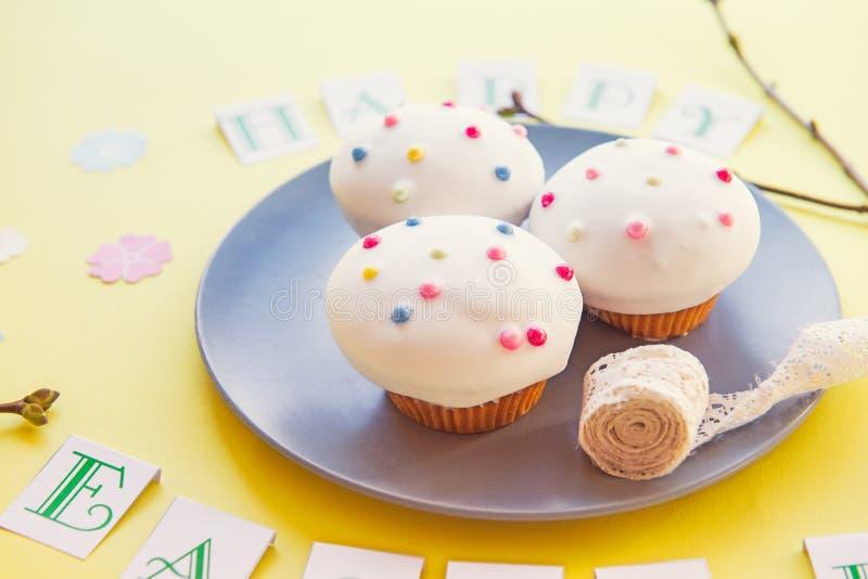Platte mit köstlichen Ostern-kleinen Kuchen und Weinleseband mit glücklicher Ostern-Beschriftung, neue Niederlassungen mit Nieren stockfoto