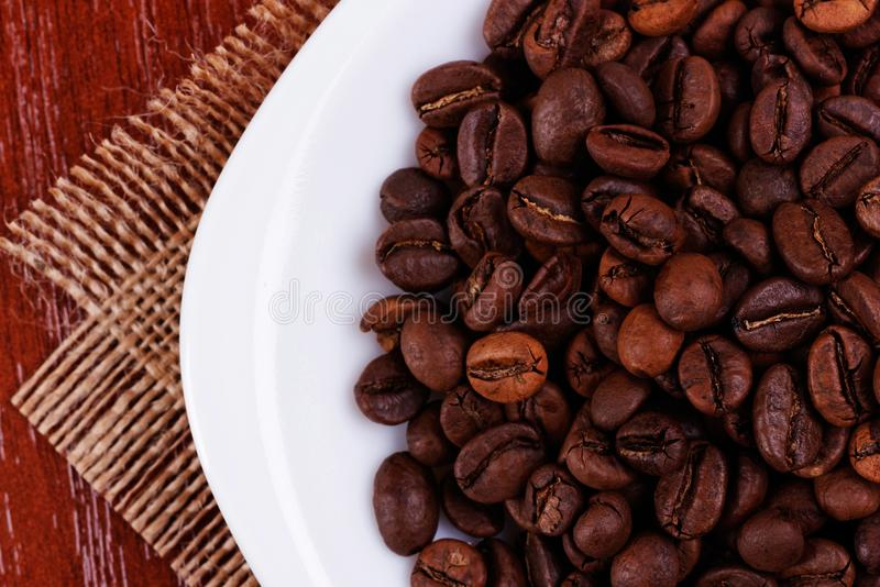 Platte mit mit Kaffeebohnen eine Spitzen-cpncept Ansicht stockbild
