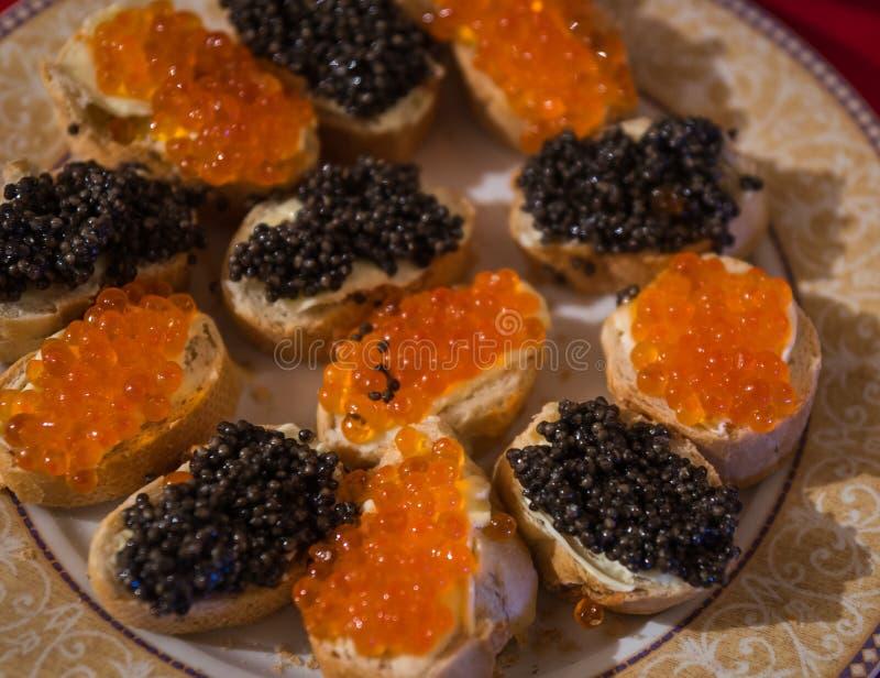 Platte mit Sandwichen mit rotem und schwarzem Kaviar stockfoto