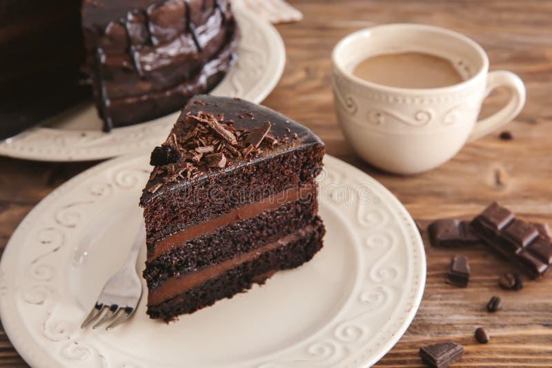 Platte mit Stück des köstlichen Schokoladenkuchens und -Tasse Kaffees auf Holztisch stockfoto
