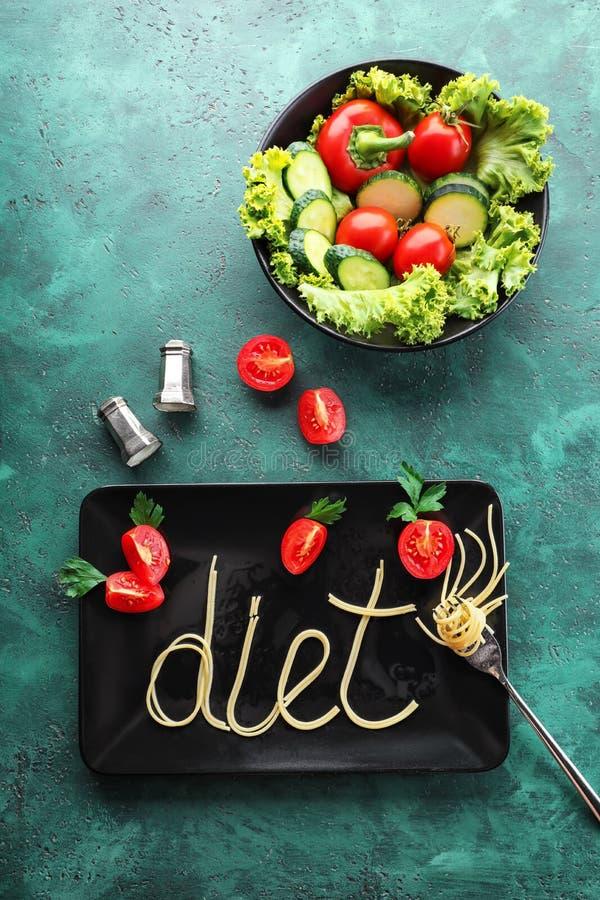 Platte mit Wort DIÄT gemacht von den Teigwaren mit Gemüse auf Farbtabelle lizenzfreies stockfoto