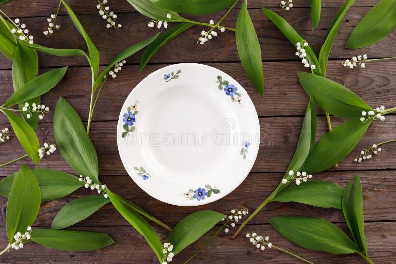 Platte und Dekor von Maiglöckchenblumen auf dem Hintergrund von hölzernen Brettern der Weinlese Weinlesehintergrund mit Blumen un lizenzfreies stockbild