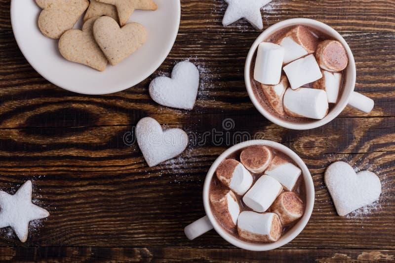 Platte von den Weihnachtsplätzchen besprüht mit Puderzucker und Schalen heißer Schokolade mit Eibischen auf Holztisch lizenzfreies stockfoto