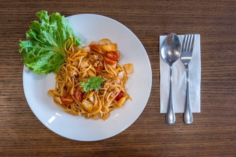 Platte von köstlichen italienischen Spaghettis mit Tomatensauce und von frischem Basilikum auf Holztischhintergrund stockfoto