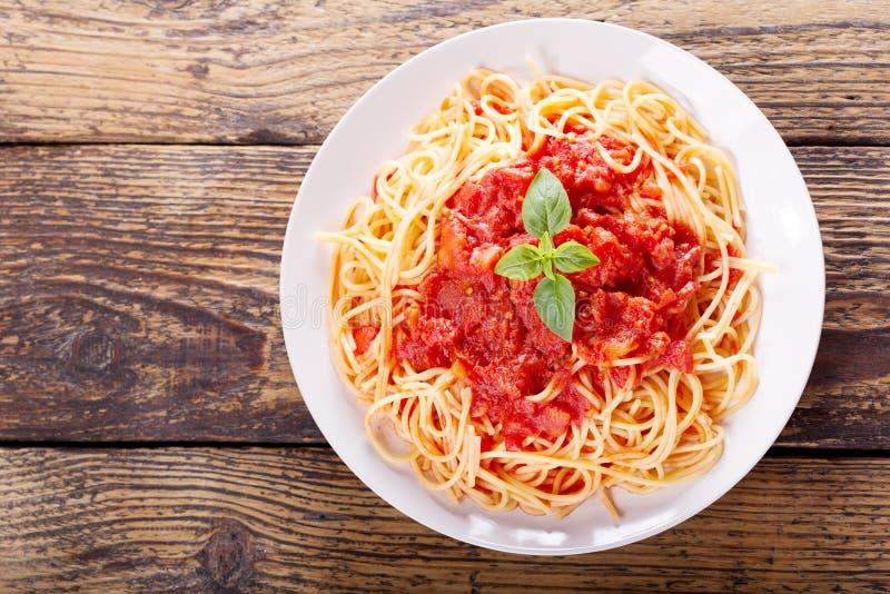 Platte von Teigwaren mit Tomatensauce und grünem Basilikum lizenzfreie stockbilder