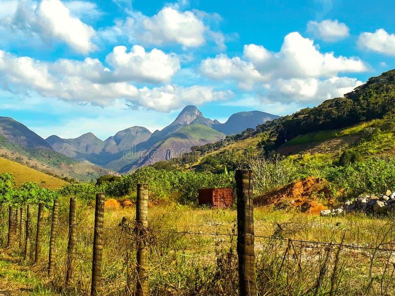 Platteland, mooi groen landschap met houten omheining, prikkeldraad en bergen op de achtergrond royalty-vrije stock afbeelding