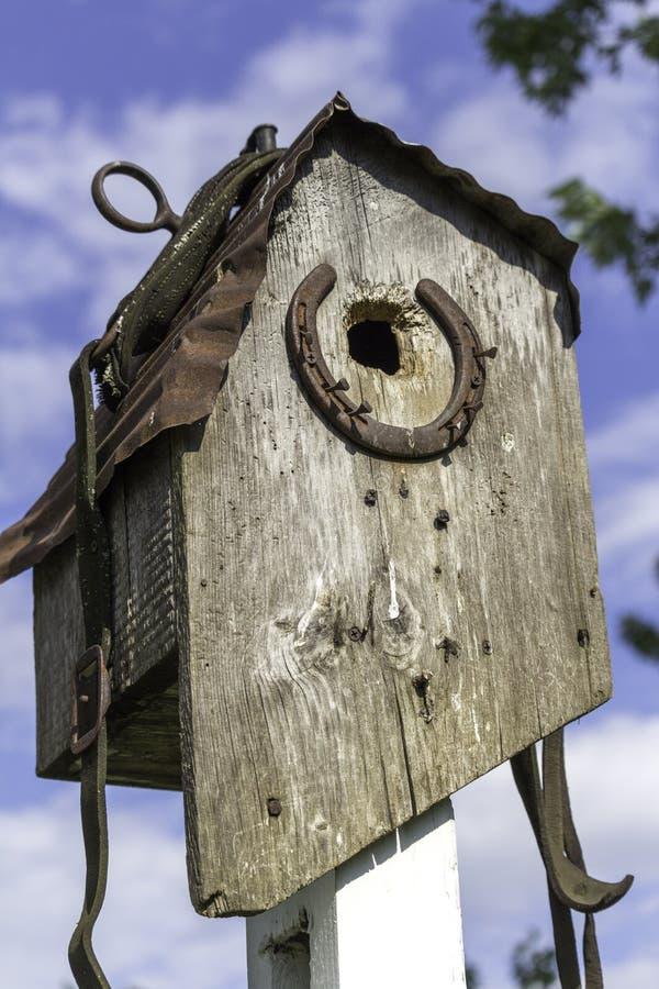 Plattelander doorstaan houten vogelhuis met van het paardschoen en leer riemen stock afbeeldingen