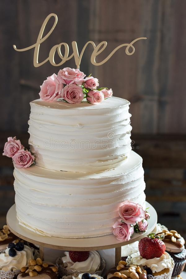 Plattelander verstoorde huwelijkscake met liefde topper en verse roze rozen royalty-vrije stock fotografie