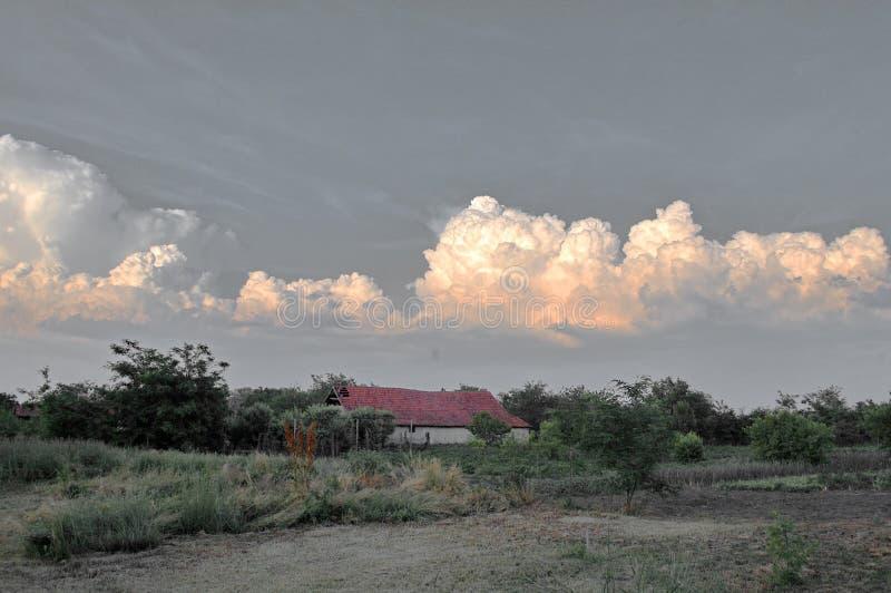 Plattelandshuis met stormachtige wolken en hemel op achtergrond stock fotografie