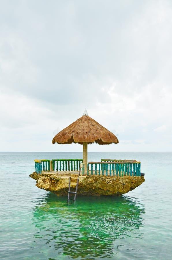 Plattelandshuisje bovenop de rots met zeewater wordt omringd dat stock foto