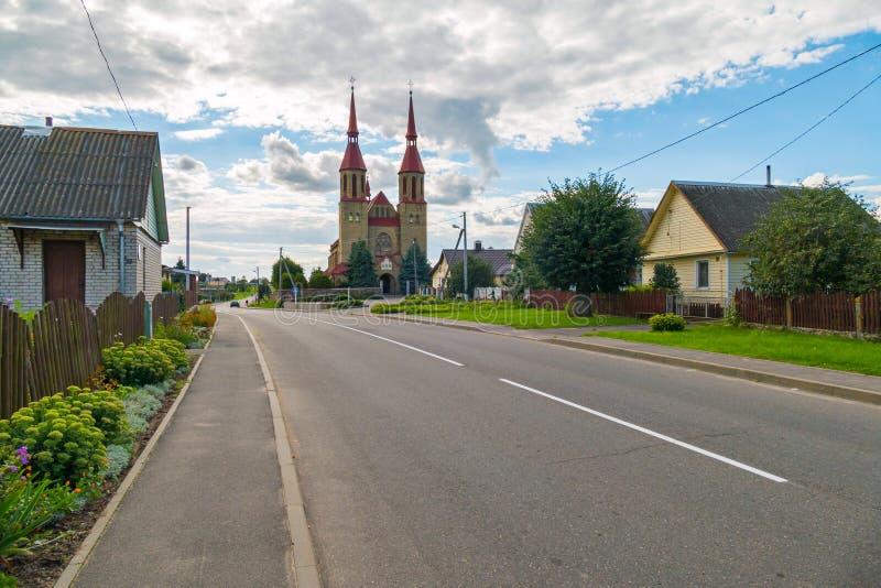 Plattelandshuisjes op de achtergrond van een lange kerk met een rood dak royalty-vrije stock afbeeldingen