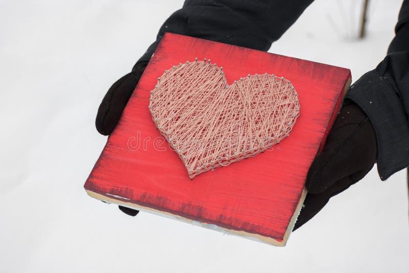 Platten des Fadens und der Nägel, Herz auf einem roten Hintergrund Schnurkunst auf einem weißen Hintergrund in den Händen Geschen lizenzfreie stockbilder