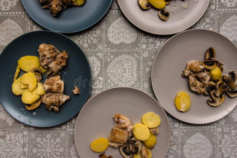 Platten des Hühnerfleisches mit Pilzsoße und -kartoffeln auf dem Tisch mit einer grauen Tischdecke stockbilder