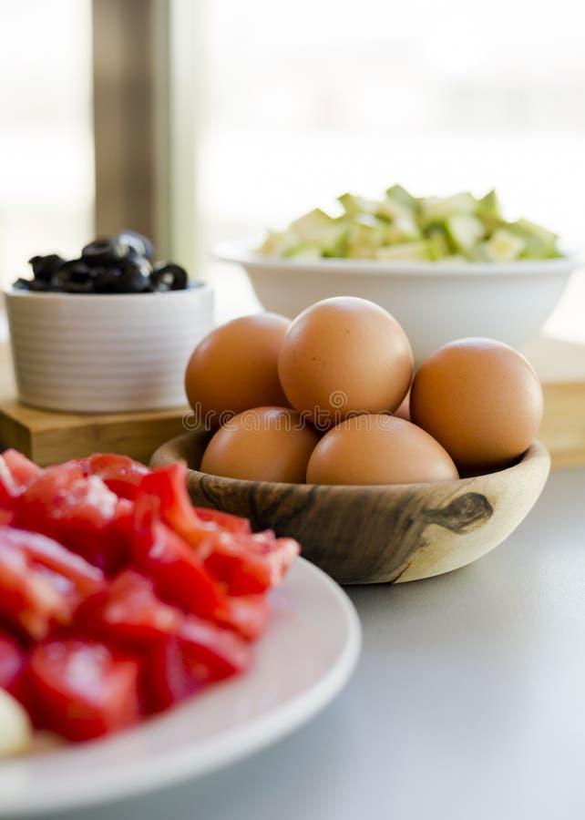 Platten mit geschnittenem Gemüse und Eiern mit Oliven in den Schüsseln auf Küchentisch stockfoto
