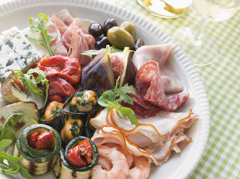 Platter of Antipasto. A Platter of Antipasto with a drink in background stock photography