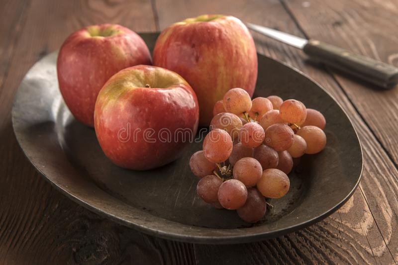 A platter of apples and grapes stock images