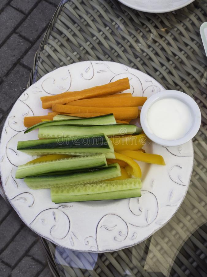 Platter of assorted fresh vegetables with yogurt dip on white plate royalty free stock images