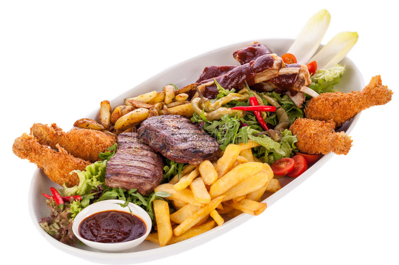 Platter of mixed meats, salad and French fries. Wholesome platter of mixed meats including grilled steak, crispy crumbed chicken and beef on a bed of fresh leafy stock images