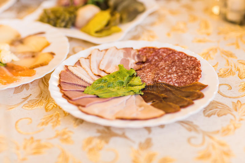 Platter of sliced ham,salami and cured meat with vegetable decoration on festive table royalty free stock photo