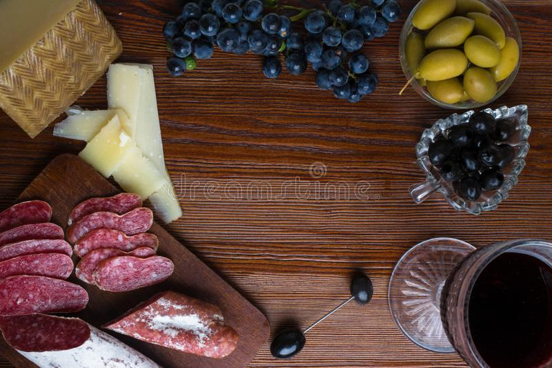Platter with sliced Italian hard cheese pecorino toscano, homemade dried meat salami, glass of red wine, grape, olives on wooden b royalty free stock images
