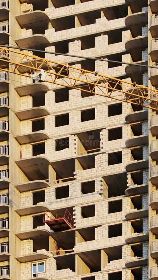 plattform för att ta den tunga påfyllningen med en kran i lägenheten för konstruktionsmång--våning byggnad royaltyfri foto