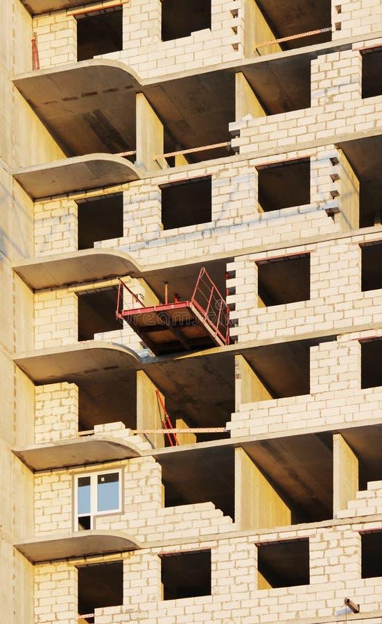 plattform för att ta den tunga påfyllningen med en kran i lägenheten för konstruktionsmång--våning byggnad arkivbild