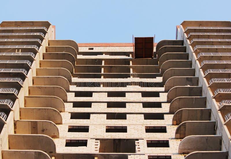 plattform för att ta den tunga påfyllningen med en kran i lägenheten för konstruktionsmång--våning byggnad royaltyfri bild