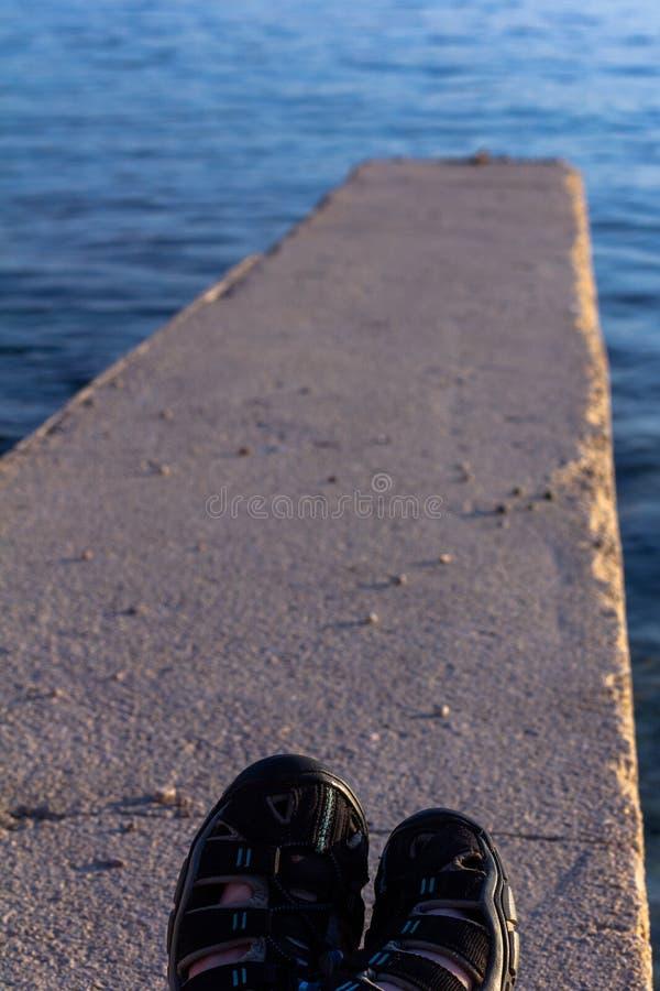 Plattierte Füße der Sandale, die auf einer konkreten Anlegestelle unterstreicht zu Se sich entspannen lizenzfreies stockbild