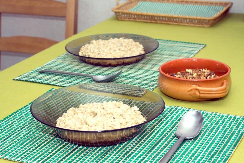 Plattor med havregröt och bruntlera bowlar med valnötter för att frukostera royaltyfri foto