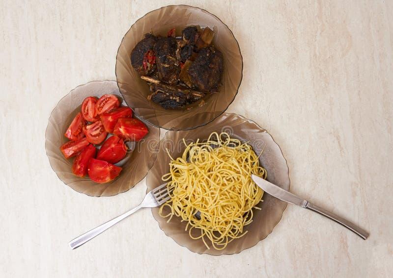 Plattor på tabellen med stekt kött, pasta och arkivfoto