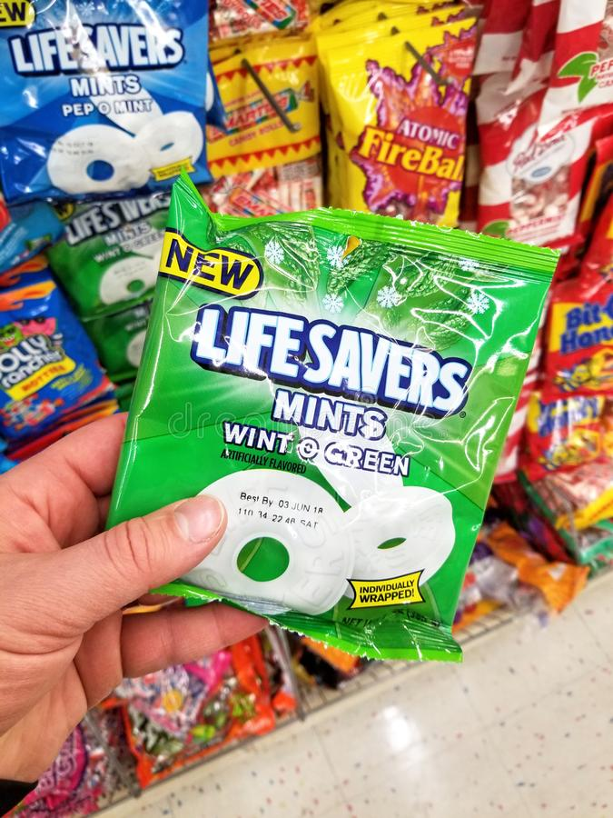 A hand holding Life Savers hard candy pack. PLATTSBURGH, USA - SEPTEMBER 10, 2018: A man holding Life Savers pack Mints. Life Savers is an American brand of stock photos