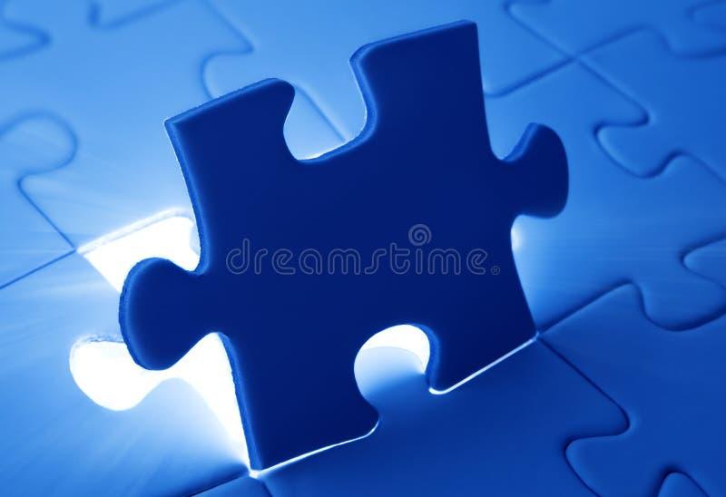Platzierung des letzten Stückes des Puzzlen lizenzfreie stockbilder