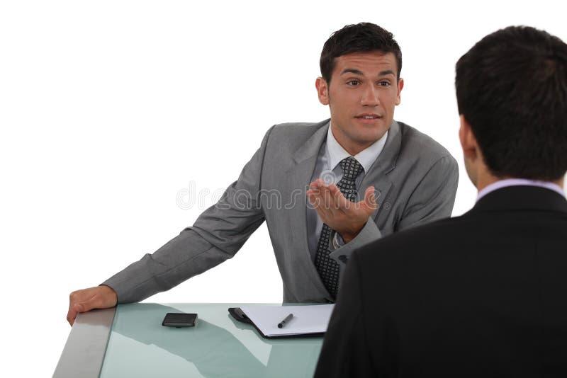 Plaudern mit zwei Geschäftsmännern lizenzfreies stockfoto