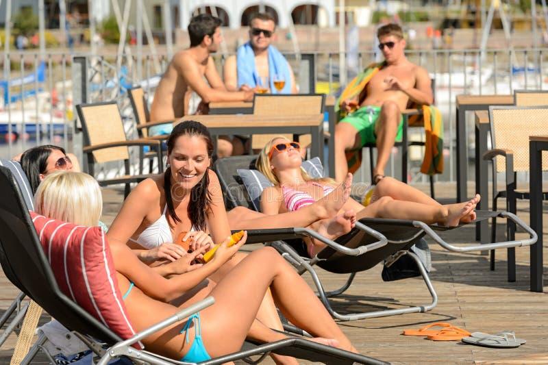 Plaudernde Mädchen, die auf dem ein Sonnenbad nehmenden deckchair liegen stockbild
