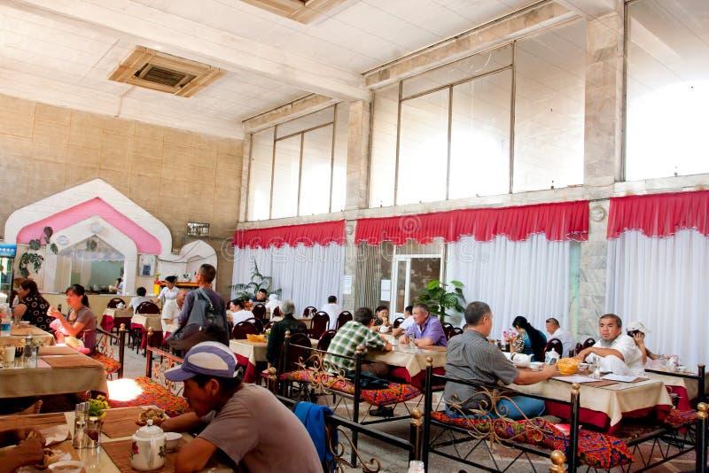Plaudernde Männer und Frauen essen im asiatischen Artteehaus mit Sofas in Zentralasien zu Abend lizenzfreie stockbilder