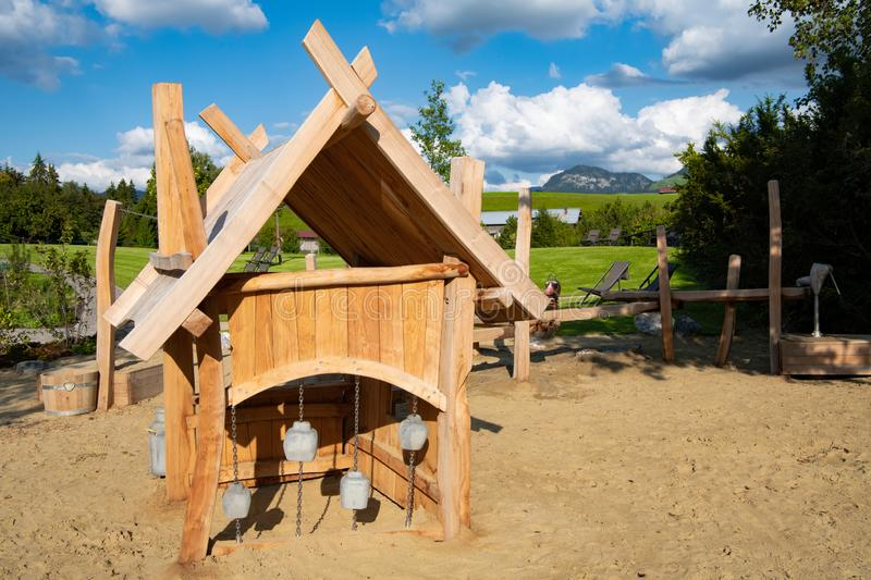 Alpine dairy on playground in German Alps. Play alpine dairy with cowbells for children in Allgäu Alps. Hotel and Resort Sonnenalp in Germany stock photos
