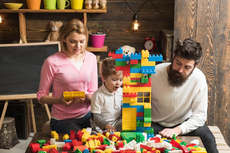 Play concept. Learn through play. Little son with mother and father play with toy bricks. Creative family play royalty free stock images