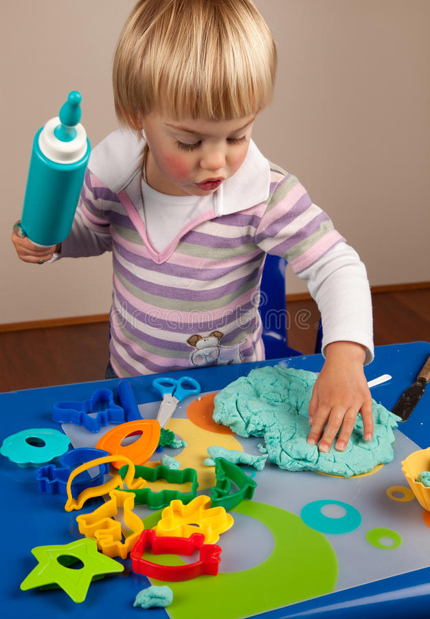 Play dough. Little girl playing with play dough stock images