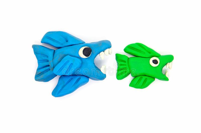 Play dough big fish eat little fish on white background.  stock photography