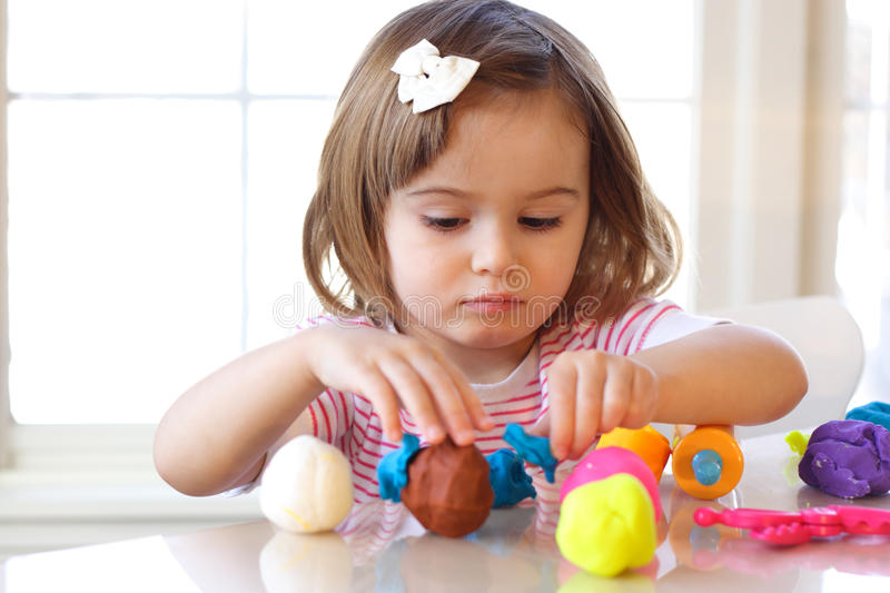 Play dough game. Little girl creating toys from play dough royalty free stock photos