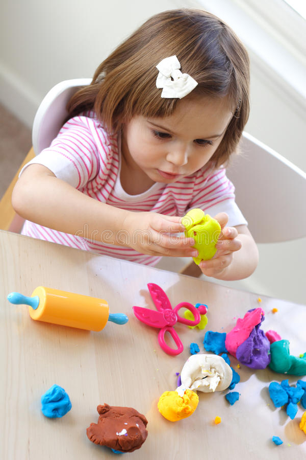 Play dough game. Little girl creating toys from play dough royalty free stock photography