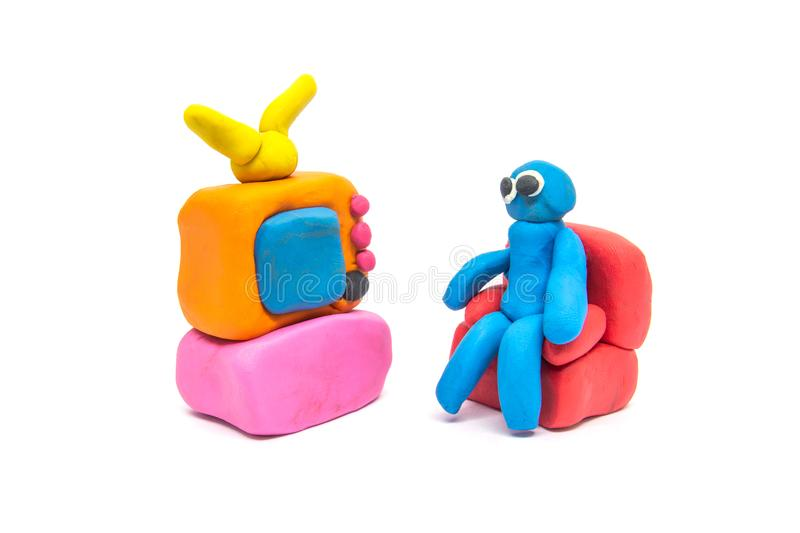 Play dough man sitting on red sofa on white background.  stock photo