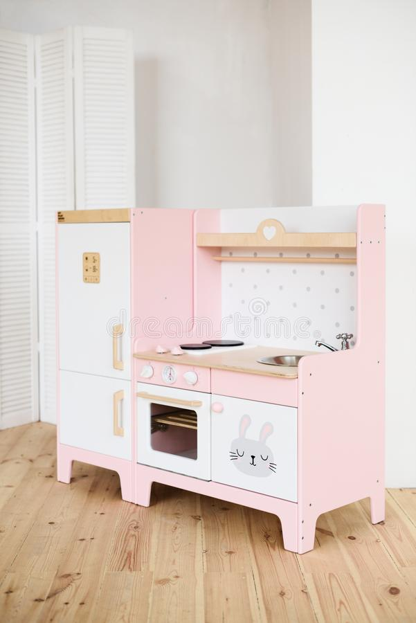 Play furniture for children. Sweet little pink kitchen with fridge, stove, oven and sink in light room royalty free stock photos